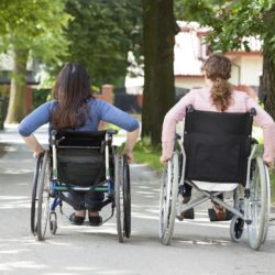 Back view of two women on wheelchairs in park
